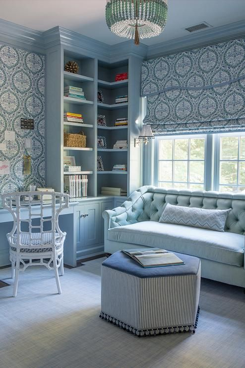a refined light blue home office with printed wallpaper and curtains, a light blue sofa, a white chairs