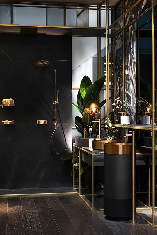 a refined modern bathroom done in black and gold, with gold sinks and fixtures, with catchy lamps and potted plants