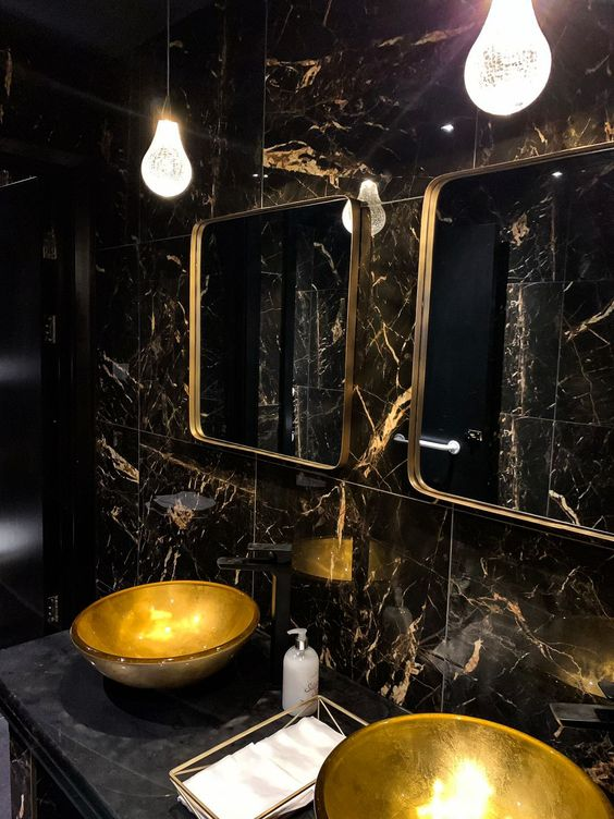 a refined powder room with black marble tiles, gold sinks, gold frame mirrors and catchy pendant lamps