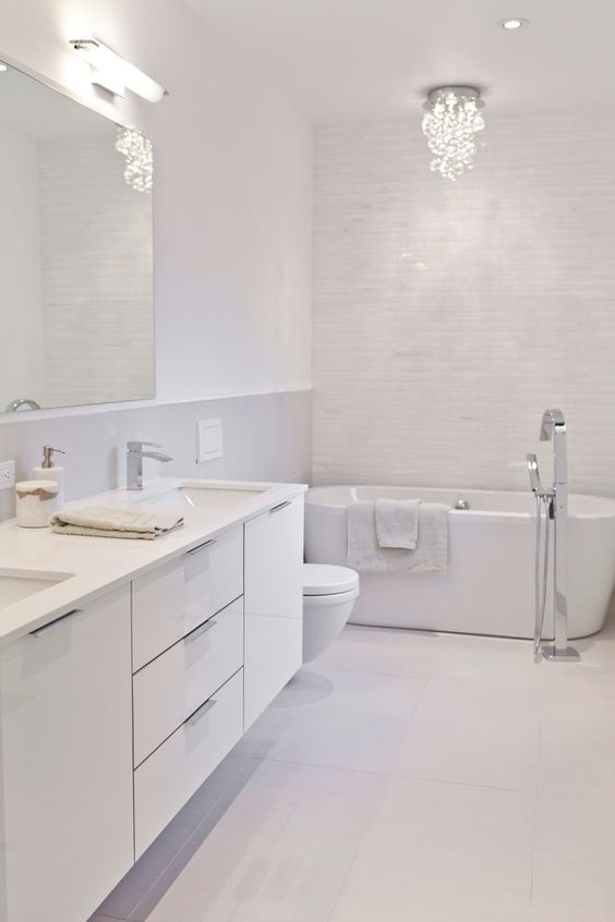 a refined white bathroom clad with tiles of various sizes, with a chic chandelier and a large white vanity