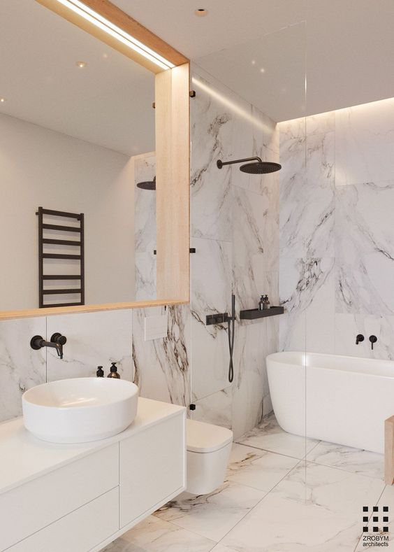 a refined white bathroom done with large scale marble tiles, with black fixtures and a large mirror in a wooden frame