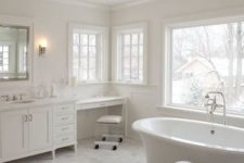 a refined white bathroom with marble tiles, a refined chandelier, a large vanity and makeup nook and windows for light and views