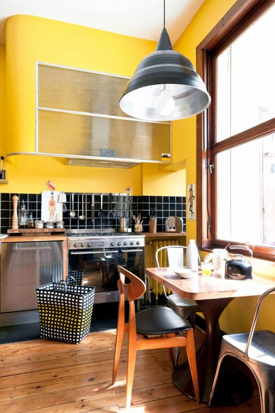 a retro kitchen done in bright yellow and black, with chic mid-century modern furniture and touches of warm stained wood