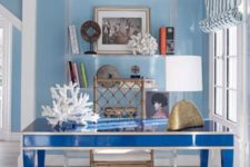 a seaside blue home office with light blue walls, a bright blue desk, an acrylic shelf and corals for a coastal feel