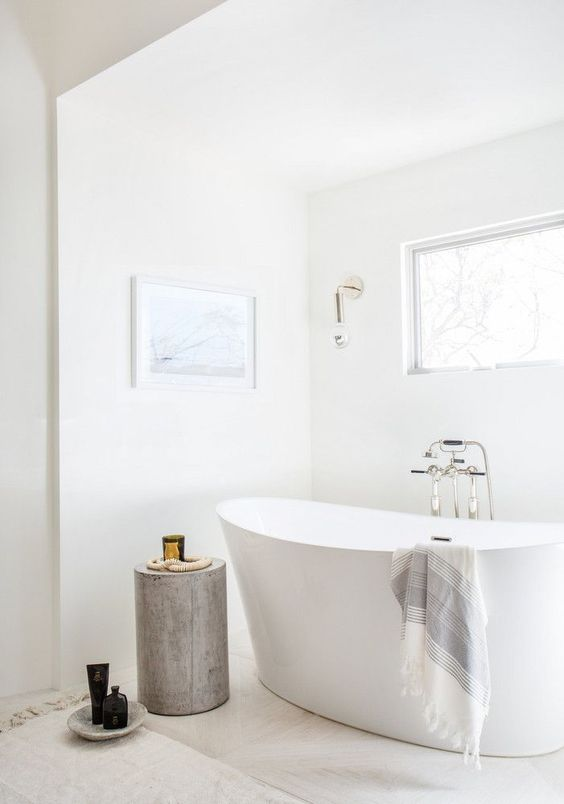 a serene white bathroom with marble tiles on the floor, a tub, a wooden stool, a window and some wall sconces