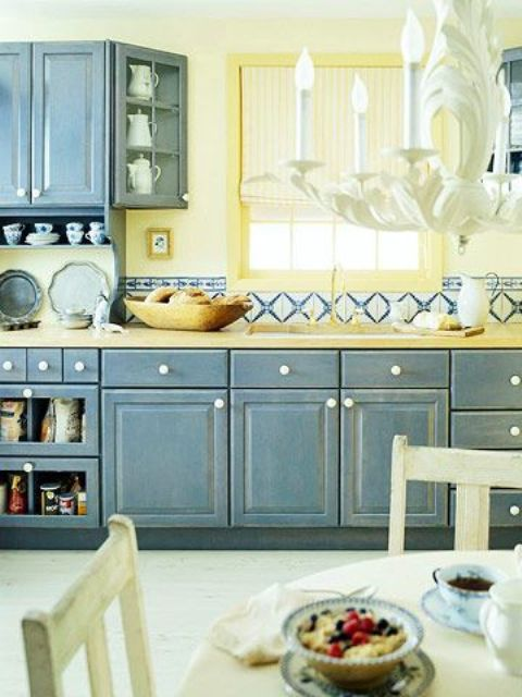 a shabby chic kitchen with shabby blue cabinets, a light yellow backsplash and bright mosaic tiles for a a bold look