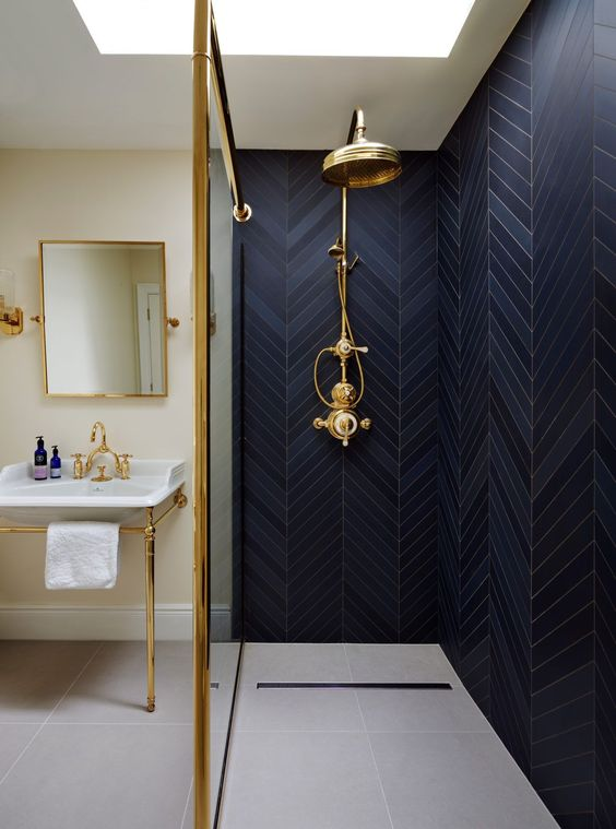 a shower clad with navy tiles in a herringbone pattern, with gold fixtures and gold lamps for a chic look