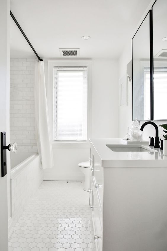a simple white bathroom done with marble subway tiles and hex ones plus a white vanity and a window for some natural light