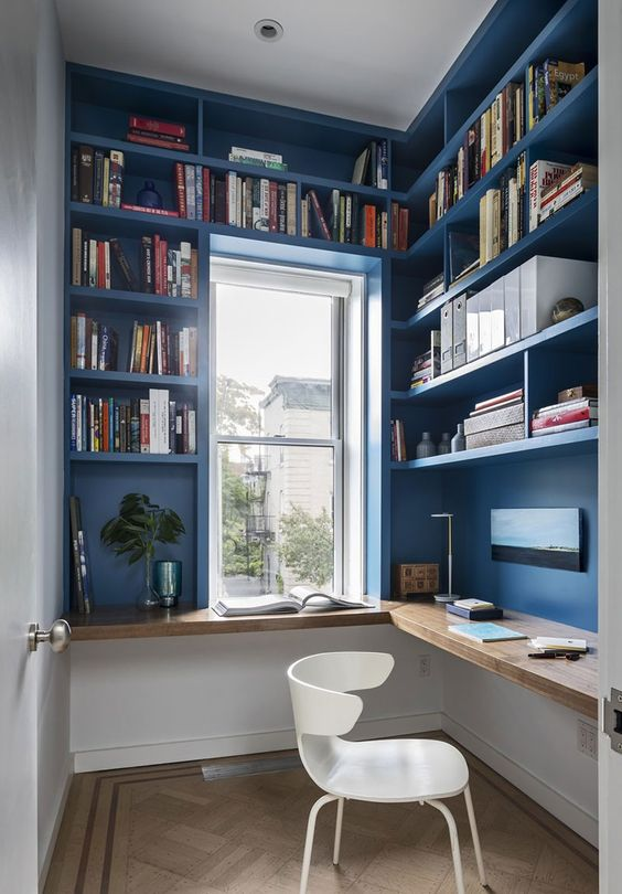 a small and bright home office, all the walls are taken by storage unit, a floating desk and a white chair