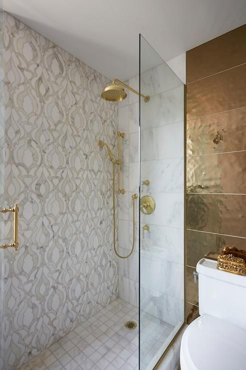 a small bathroom with neutral printed tiles, gold fixtures, a dark gold tile wall and more accents looks wow