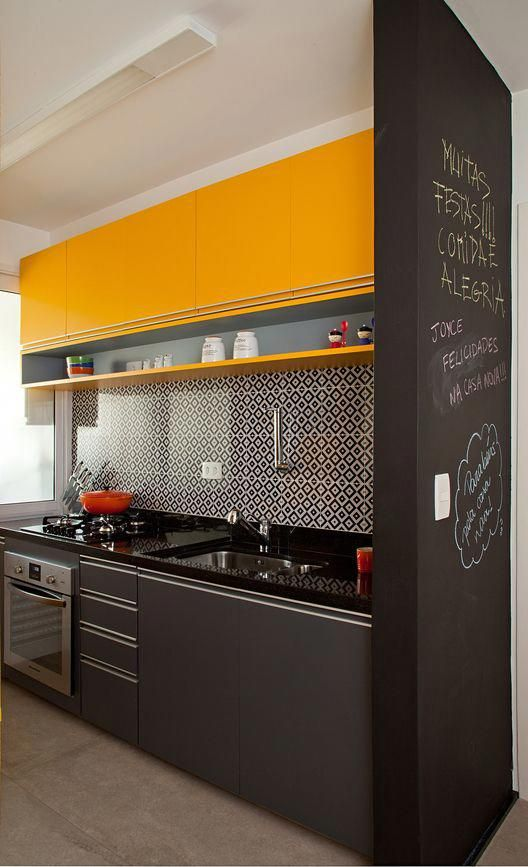 a small black and yellow kitchen with bright upper cabinets, lower grey ones, a mosaic tile backsplash and a chalkboard wall to make notes