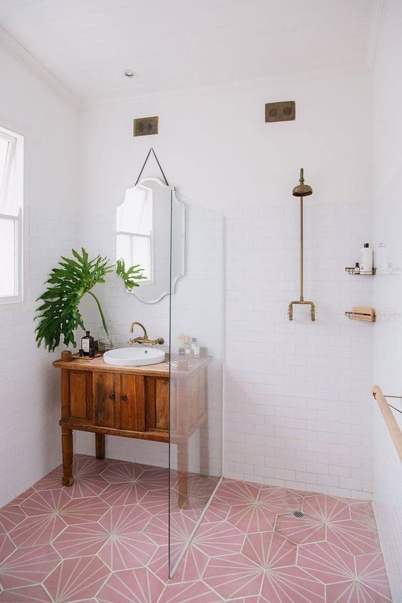 a small contemporary bathroom with a pink tile floor and brass and pink touches and fixtures for a bold look