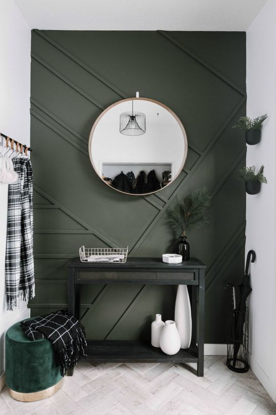 a small modern entryway with a statement graphite grey paneled wall and a matching ottoman for a chic look