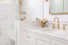 a small white bathroom with a white marble tiles and a countertop, brass and gold fixtures, frames and sconces