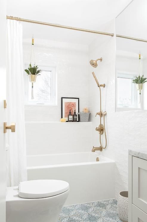 a small white bathroom with brass and gold fixtures and knobs, with a curtain rod and a gold planter to spruce up the space