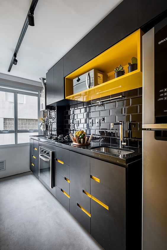 a statement black kitchen with a bright yellow shelf and yellow cutouts on the cabinets plus a glossy tile backsplash
