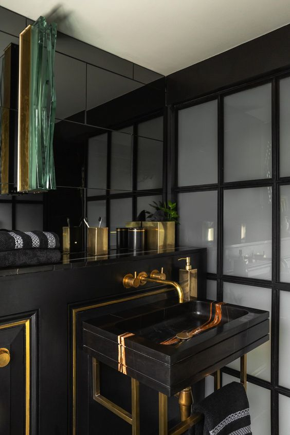 a stylish and luxurious powder room in black and gold, with gold framing and accessories plus a chic marble sink