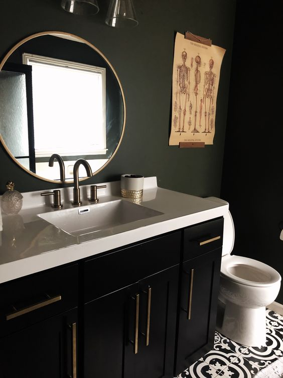 a stylish and moody bathroom with matte black walls, a black vanity, a white stone countertop and catchy artworks
