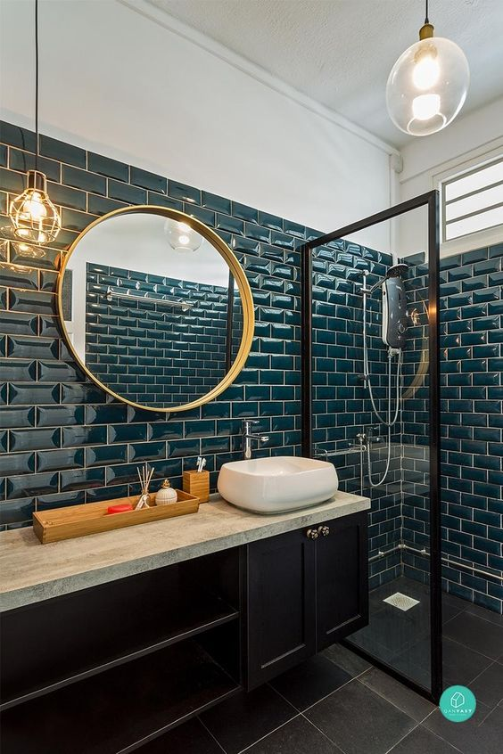 a stylish bathroom clad with teal tiles, with a midnight blue vanity, gold fixtures and a gold frame mirror