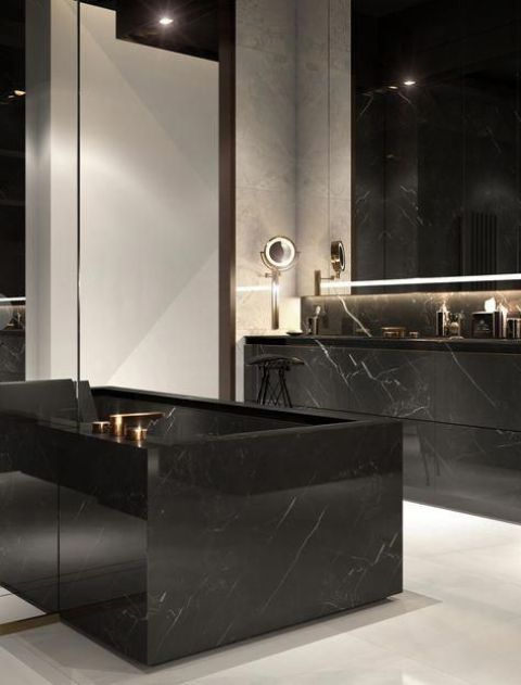 a stylish bathroom with black and white walls, a white floor, a black marble tub and vanity plus lit up mirrors