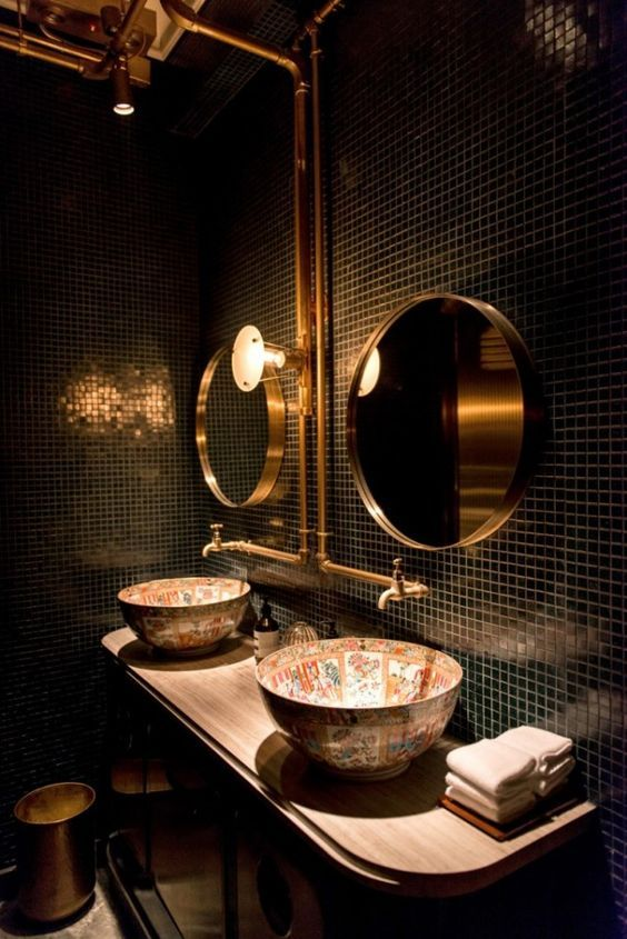 a stylish bathroom with black tiles, gold mirrors, painted sinks and exposed gold pipes is jaw-dropping