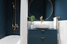 a stylish bathroom with navy walls, navy tiles, a navy vanity, gold frame mirror, gold fixtures and handles