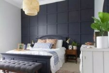 a stylish bedroom in modern and boho styles, with a black paneled wall, a black bed and a grey bench plus a wicker lamp