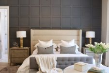 a stylish bedroom with a black paneled wall, an upholstered bed and bench, a round chandelier, wooden nightstands and layered rugs