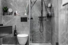 a stylish contemporary bathroom done with grey marble tiles, black fixtures and white appliaces is a chic idea