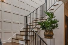 a stylish entryway with a white paneled wall that looks catchy and non-boring like many other neutral walls do