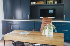 a stylish home office with a navy storage unit, a catchy industrial desk of wood and metal, a leather chair and a wicker basket