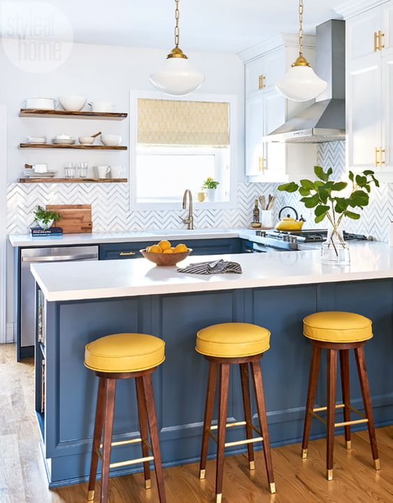 a stylish kitchen done in blue and white, with yellow stools and white countertops looks crispy fresh