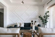 a stylish living room with a white paneled wall that makes an accent and looks bold adding style and chic to the space