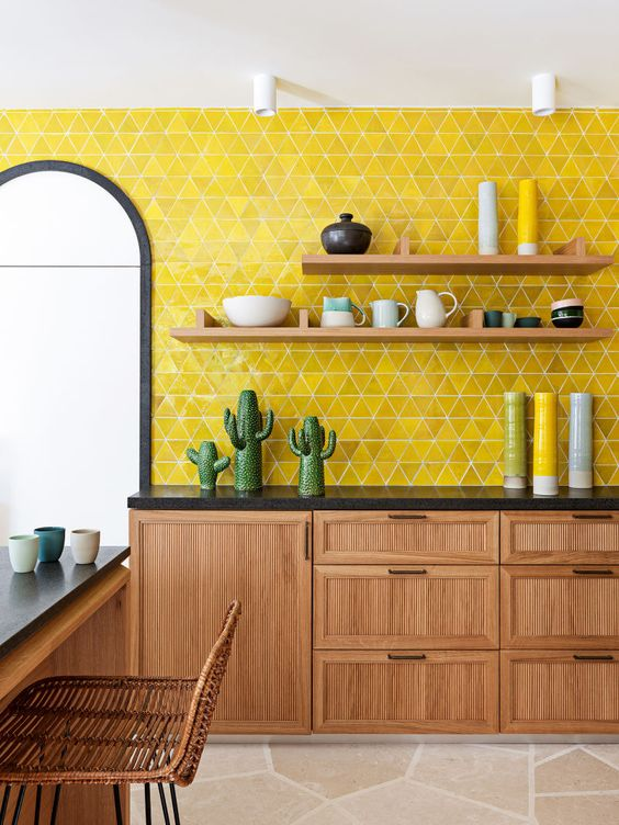 a stylish mid-century modern kitchen with wooden cabinets and furniture, black countertops and a lemon yellow tile backsplash