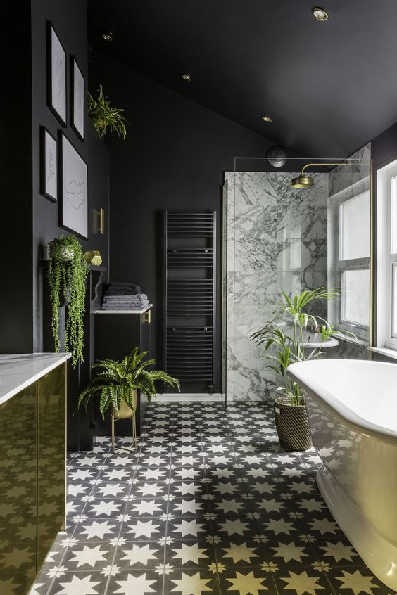 a stylish modern bathroom done with matte black walls, a gold vanity, gold planters and accessories plus cool monochrome tiles