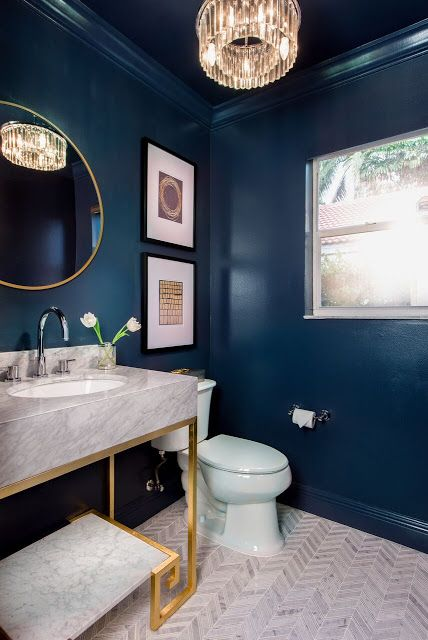 a stylish powder room with navy walls, a crystal chandelier, a gold frame mirror, a gold and white stone vanity and chic artworks