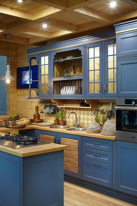a stylish vintage farmhouse kitchen with blue cabinets and buttercream yellow wooden countertops and backsplashes