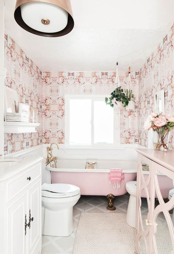 a stylish vintage inspired bathroom done with pink printed wallpaper, a pink bathtub, a pink sideboard and brass fixtures and legs