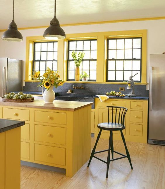 a sunny yellow kitchen with black pendant lamps, a black backsplash and countertop plus black chairs for a new take on traditional decor