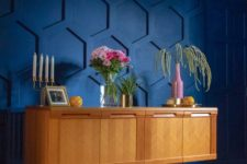 a super bold blue honeycomb paneled statement wall brings both color and pattern to the space to wow