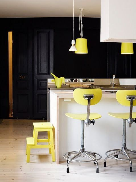 a super bold modern kitchen done with a white kitchen island, hood, black cabinetry and lemon yellow items