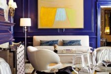 a super bold, whimsy and luxurious living room with bold blue paneled walls that make a color statement at once