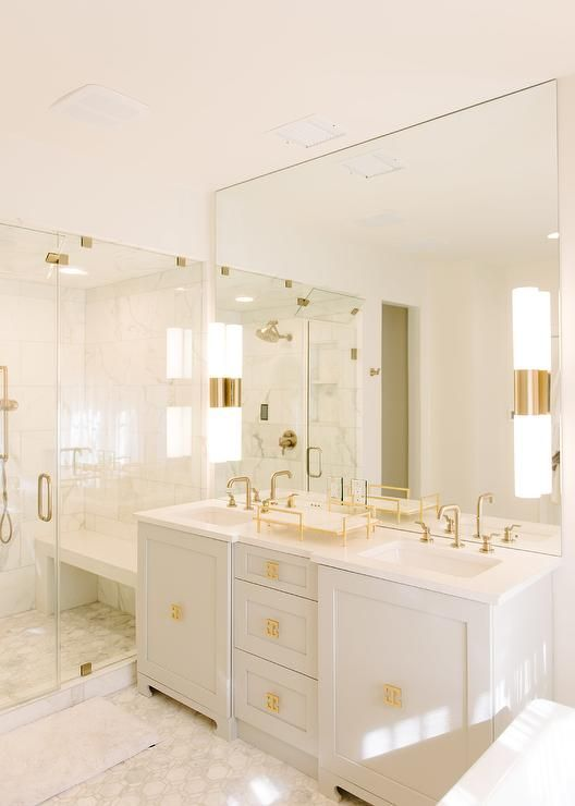 a super elegant white bathroom with chic gold fixtures, handles, knobs and other accents looks very chic