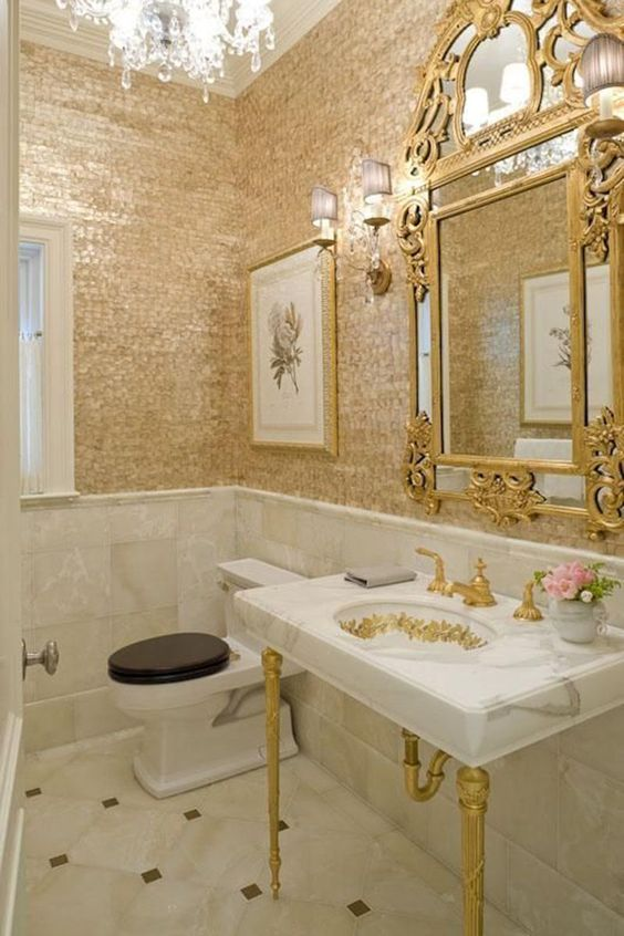 a super glam powder room with gold shingle walls, a refined mirror, a vanity with gold legs and a crystal chandelier