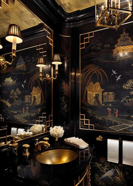 a super refined and chic black and gold bathroom with an exquisite artwork, chic lamps and chandeliers, a gold sink and fixtures