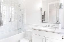 a traditional chic white bathroom with marble tiles, a tub and shower combo, with a vanity and a large mirror