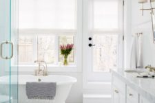 a traditional white bathroom with marble tiles clad in a chveron pattern, a tub by the window and a large vanity