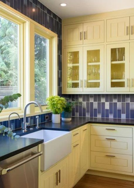 a traditional yellow and navy kitchen with navy and white tiles on the wall and backsplash