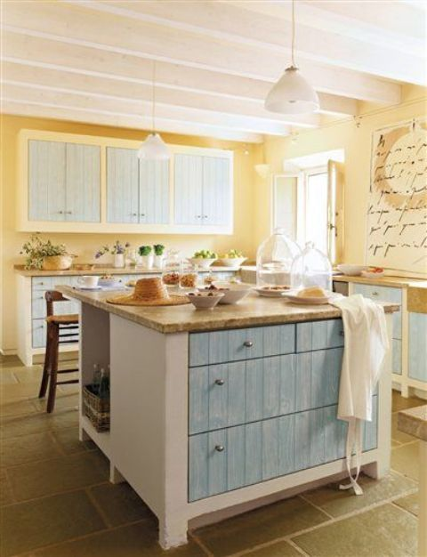 a unique vintage kitchen with light yellow walls, light blue cabinets and pendant lamps plus wooden surfaces