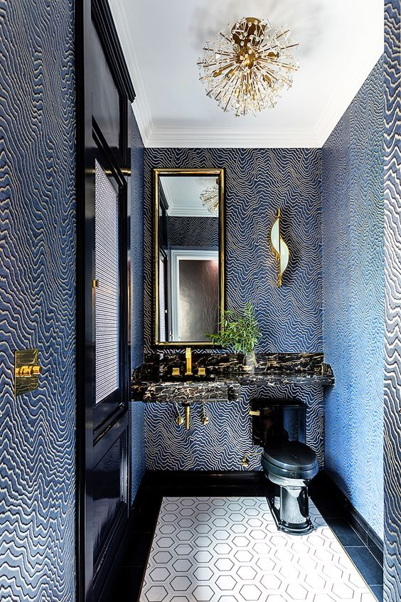 a very quirky powder room with navy and gold pritned wallpaper, a black stone vanity and a black toilet plus a unique chandelier